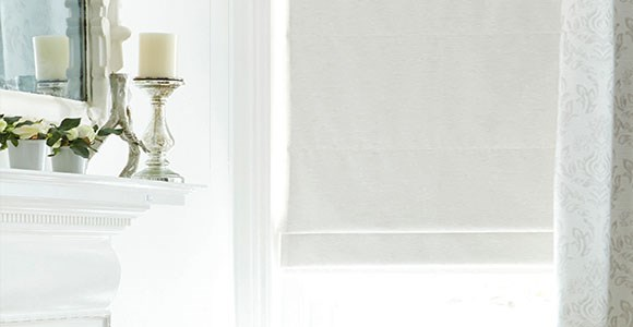 A collection of classic white roman blinds in a stylish selection of textures and fabric types.